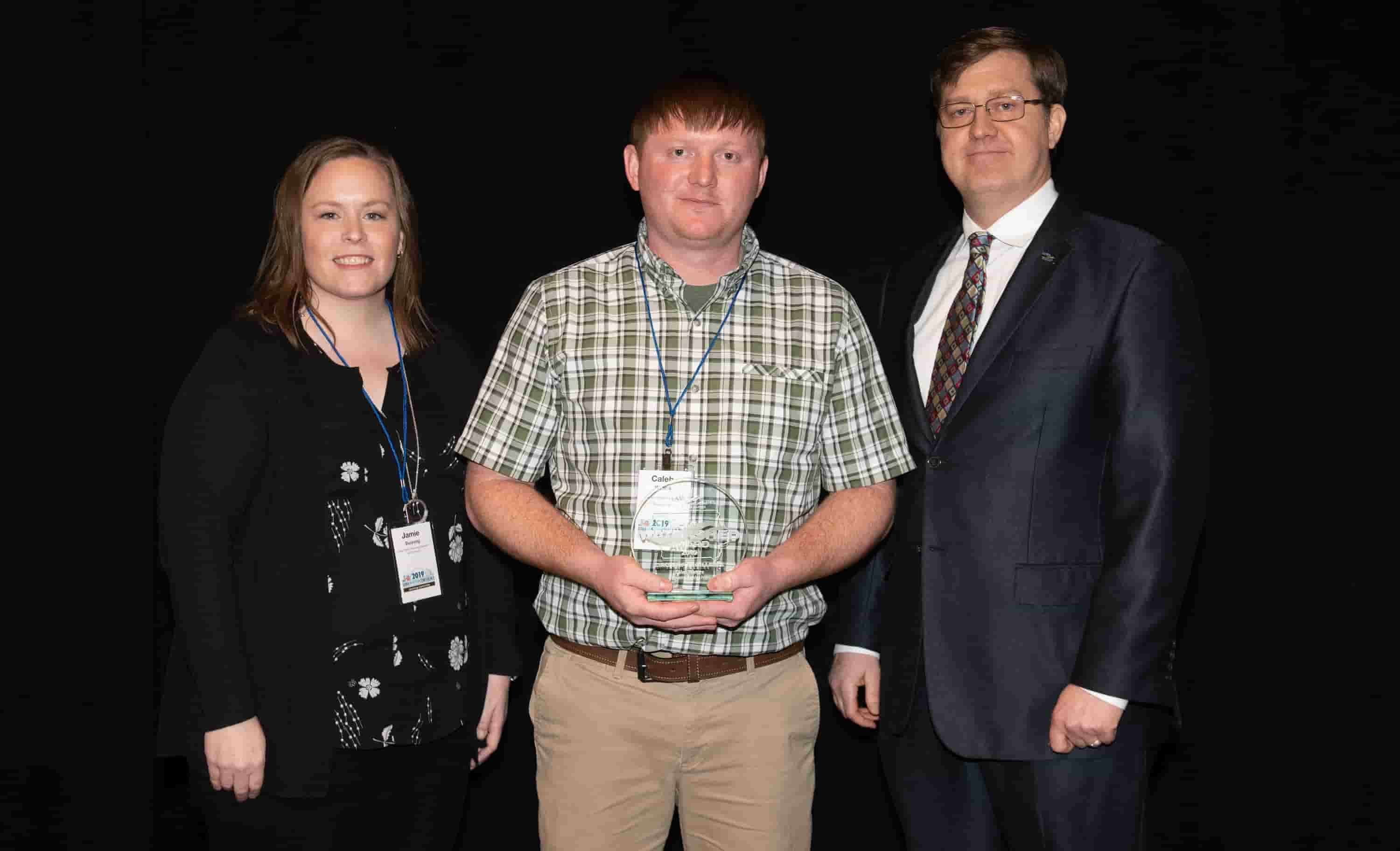 Jamie Benning with Iowa State University, Sean McMahon with Iowa Ag Water Alliance presenting Caleb Waters, watershed coordinator, with an IAWA Iowa Watershed Award