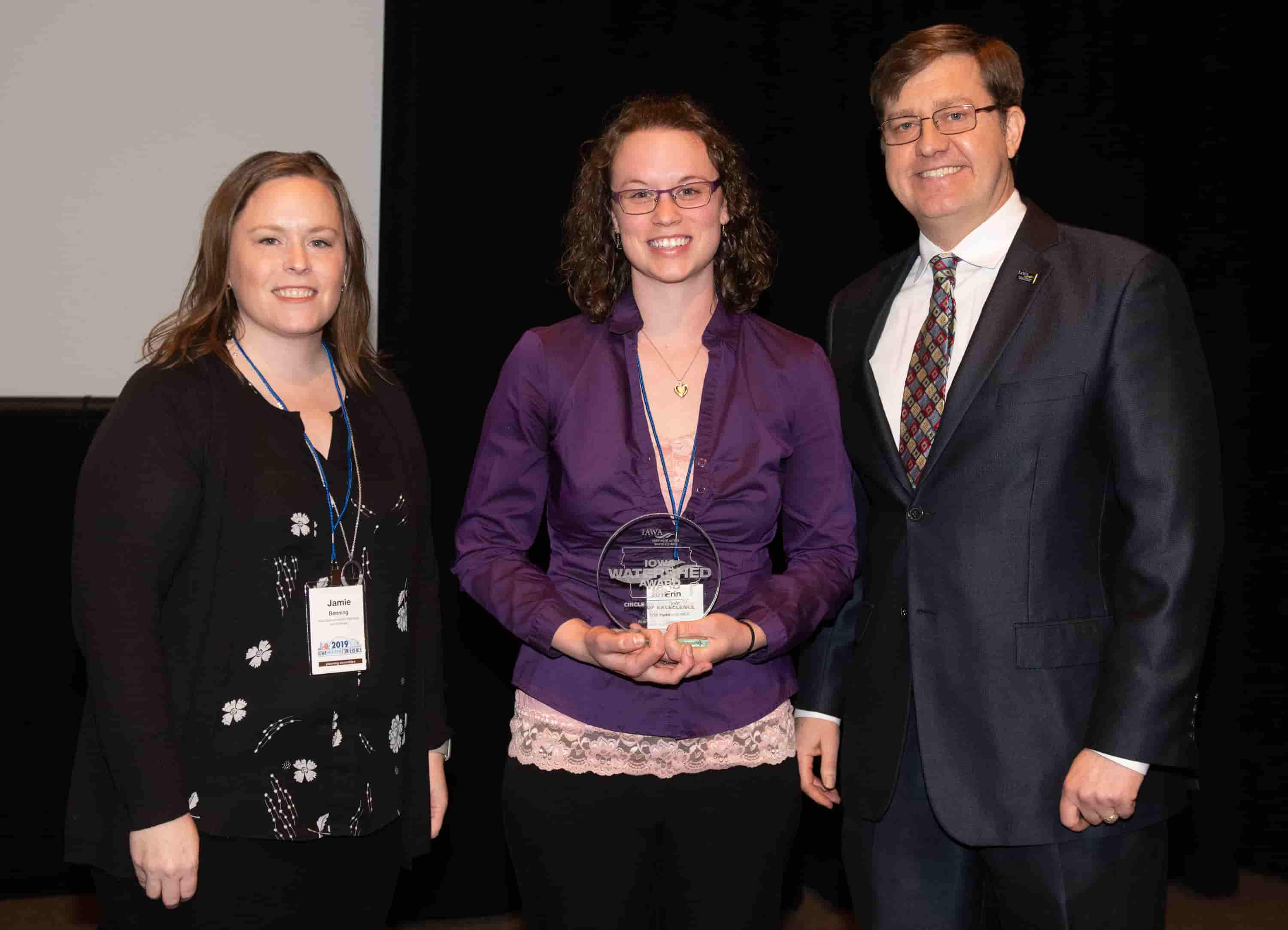 Jamie Benning with Iowa State University, Sean McMahon with Iowa Ag Water Alliance presenting Erin Ogle, watershed coordinator, with an IAWA Iowa Watershed Award