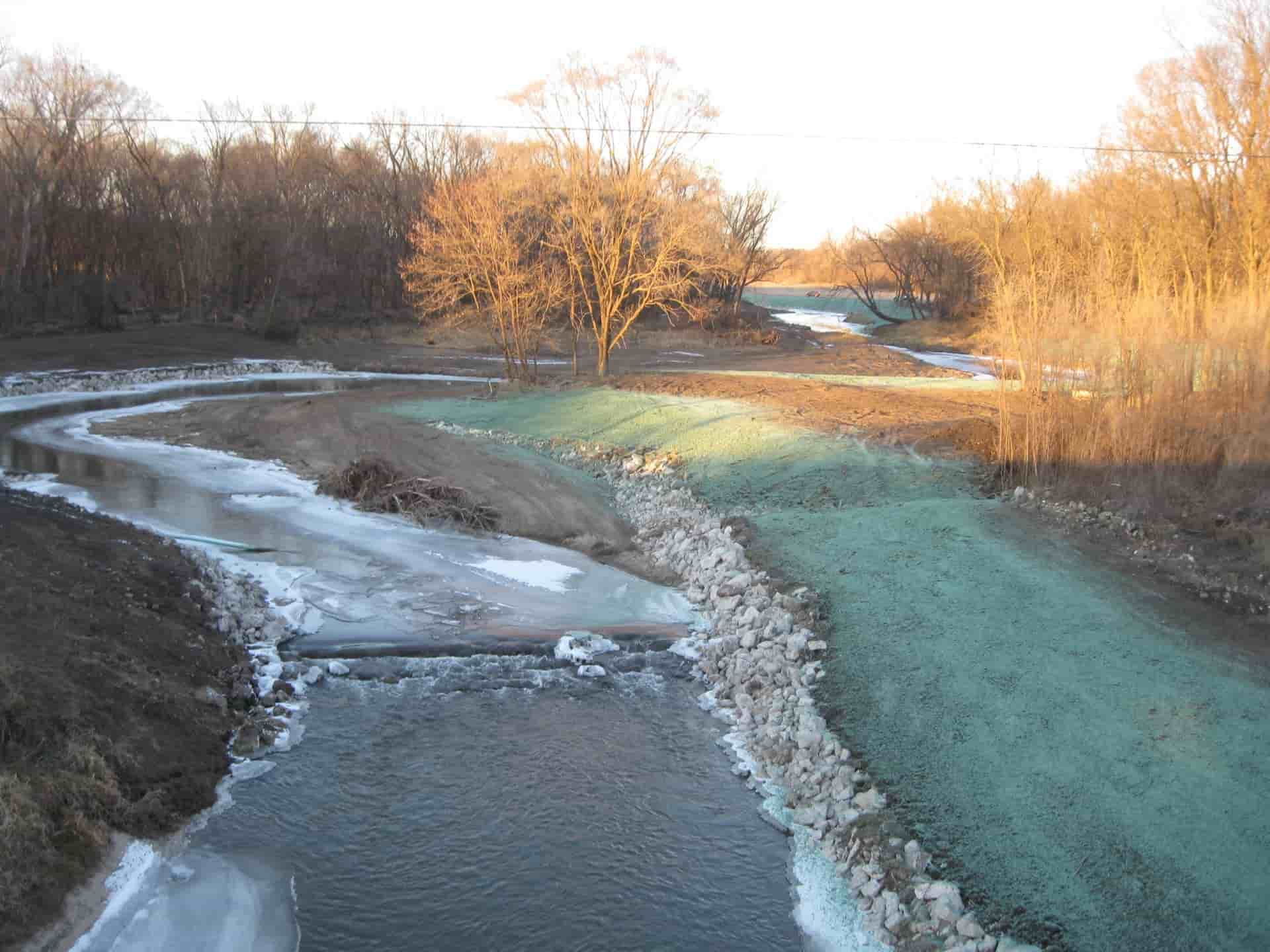 Aerial view of completed stream buffer; rocks lining stream and grass seed planted above on land