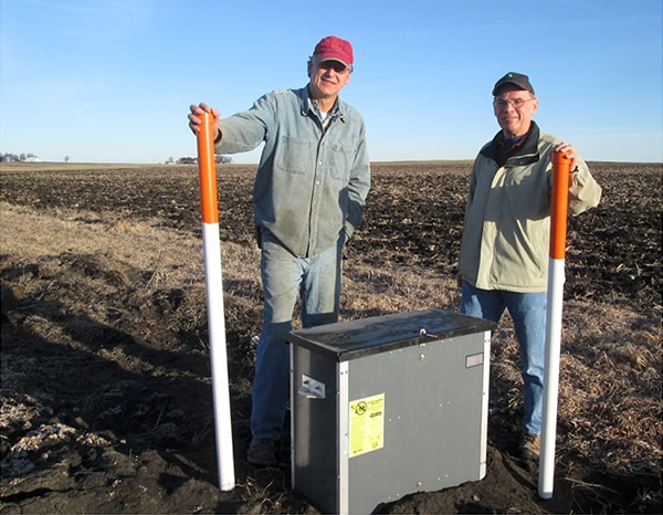Farmer Tom Vincent (right) and landowner Roger Winterhof (left) have worked together to address water quality. They installed saturated buffers (pictured in the middle of the two), an Iowa innovation.