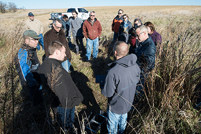 Iowa's Water Future Task Force co-chairs Larry James and Steve Bruere and a host of others listen to ISA's Keegan Kult explain how a bioreactor works to remove nitrates from water.