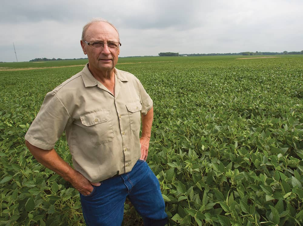 Wayne Fredericks , former Iowa Soybean President, stands in his field