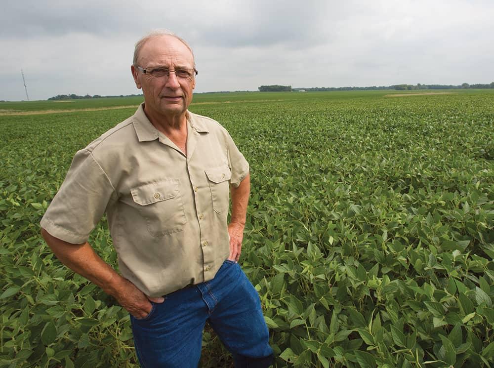 Wayne Fredericks , former Iowa Soybean President, stands in his field